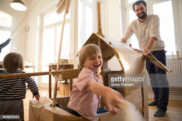 playful son and father playing with cardboard sailingboat at home - spielen stock-fotos und bilder