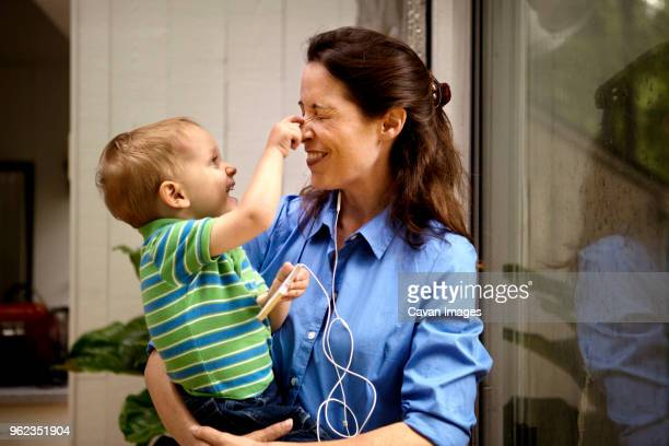 Playful son pinching mothers nose while holding mobile phone at home
