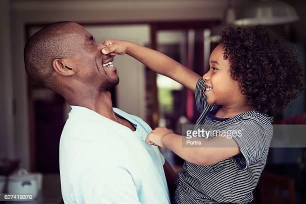 Playful son pulling father's nose at home