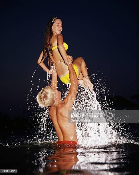 Playful teen couple splashing in water
