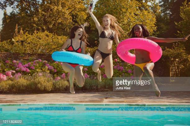 playful teenage girl friends jumping into sunny summer swimming pool - summer stock pictures, royalty-free photos & images