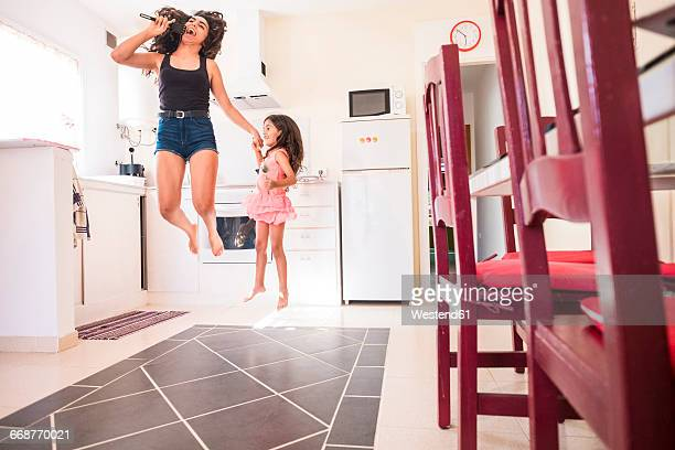 Playful teenage girl with her little sister in kitchen pretending to sing into microphone