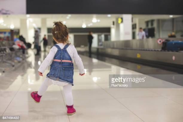 playful toddler at arrival area at airport - toddler at airport stock pictures, royalty-free photos & images