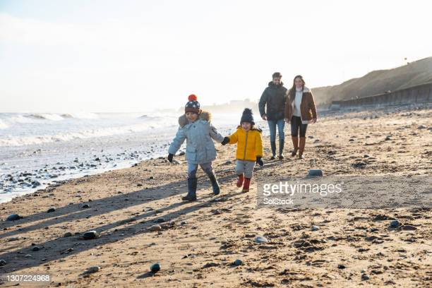 playful walks with the boys - beach stock pictures, royalty-free photos & images