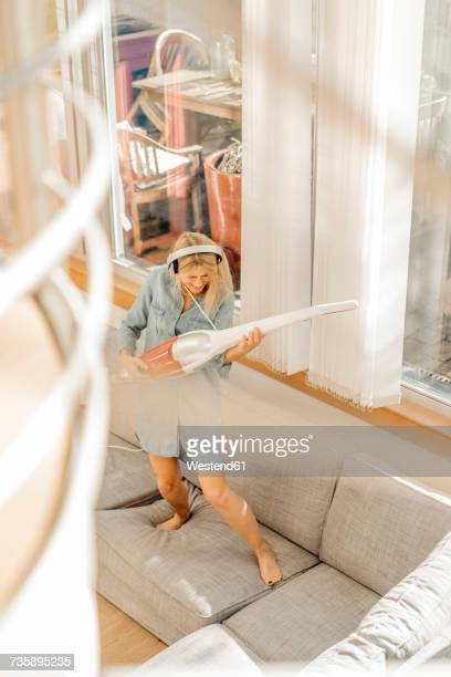 Playful woman at home wearing headphones using vacuum cleaner as air guitar on the couch