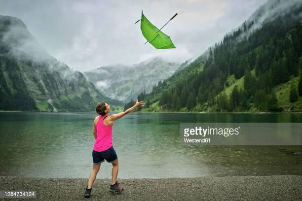 playful woman catching green umbrella at lakeshore during rainy season - fangen stock-fotos und bilder