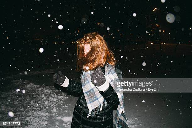 Playful Woman During Snowfall At Night