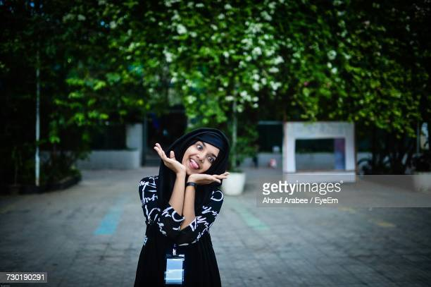 Playful Woman Gesturing While Standing At Park