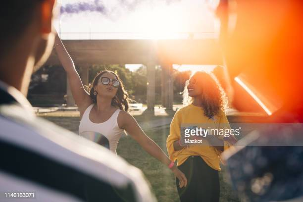playful woman having fun with friends during music festival on sunny day - arts culture and entertainment stock pictures, royalty-free photos & images