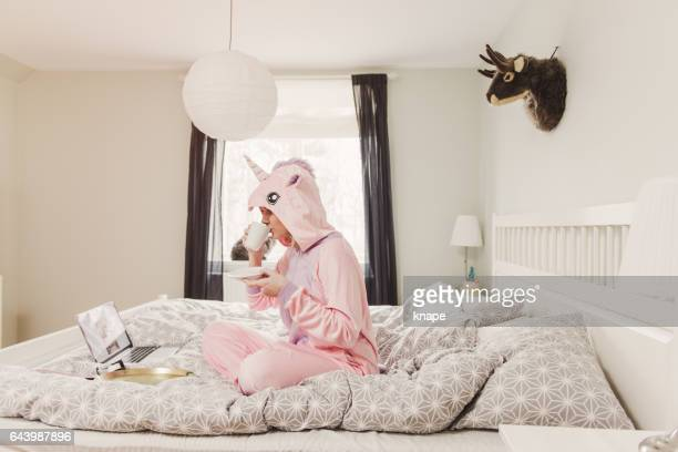 playful woman in unicorn costume in bedroom - fashion oddities stock pictures, royalty-free photos & images