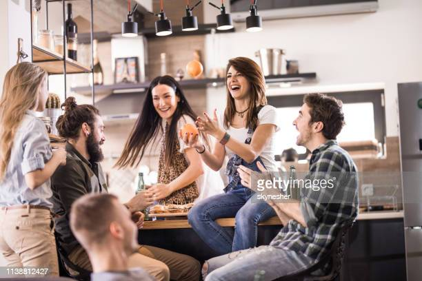 playful woman juggling with oranges and having fun with her friends at home. - roommate stock pictures, royalty-free photos & images