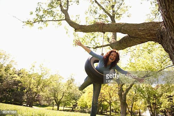Playful Woman On Tire Swing
