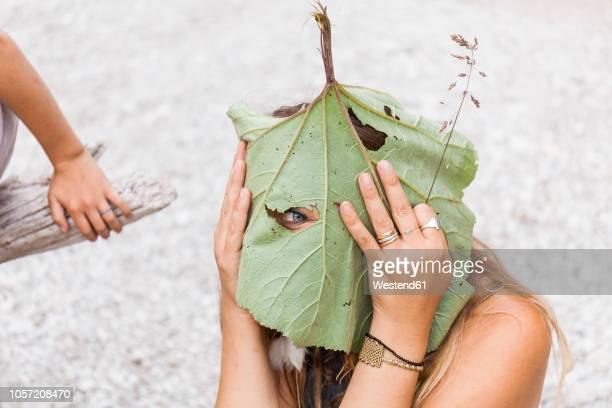 Playful woman peeking through hole in large leaf