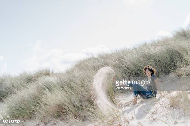 Playful woman sitting in beach dune