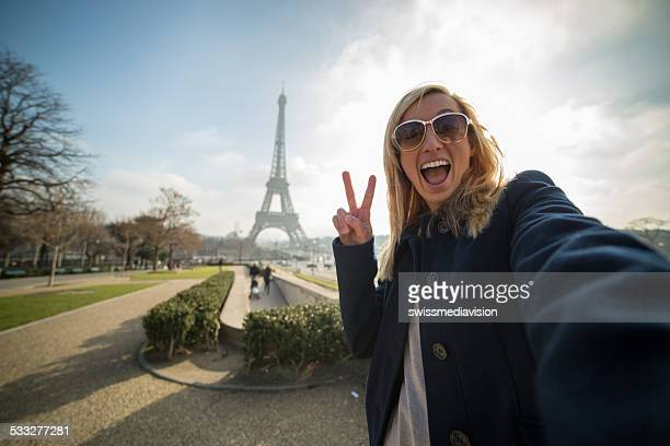 Verspielte Frau nehmen selfie am Eiffelturm-Peace-Zeichen