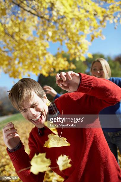 playful woman throwing leaves at man - climat stock pictures, royalty-free photos & images