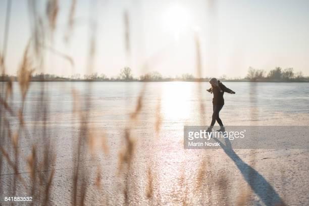 Playful woman walking alone on frozen lake