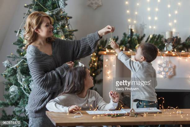 playful woman with children at home during christmas - table decoration stock pictures, royalty-free photos & images