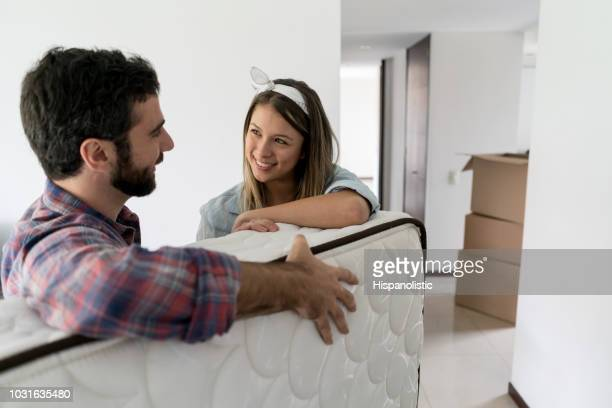 Playful woman with her partner while he is moving in a matress into their new place