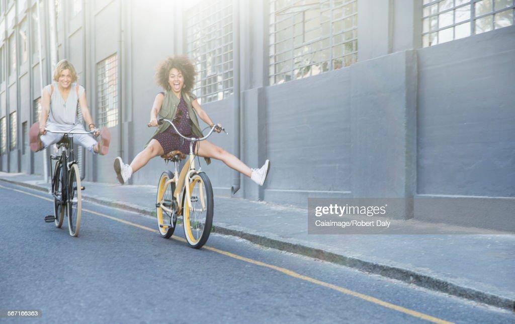 Playful women coasting on bicycles down urban street : Foto de stock