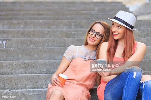 Playful women sitting on stairs and making selfie