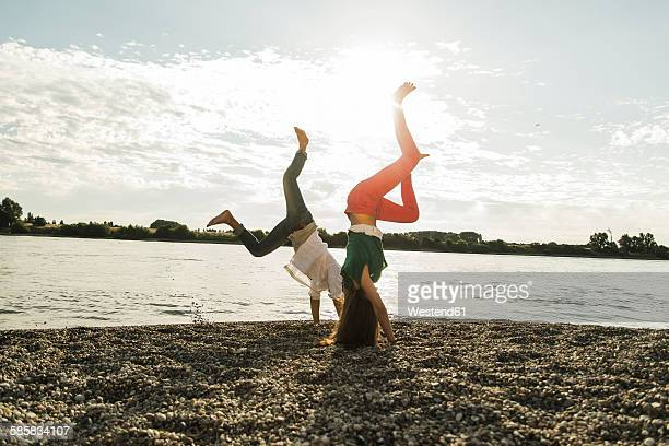 Playful young couple doing handstands by the riverside