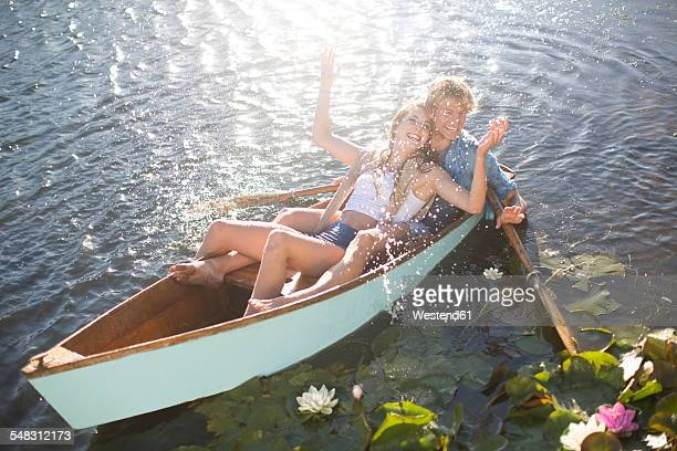 Playful young couple in a rowing boat on a lake