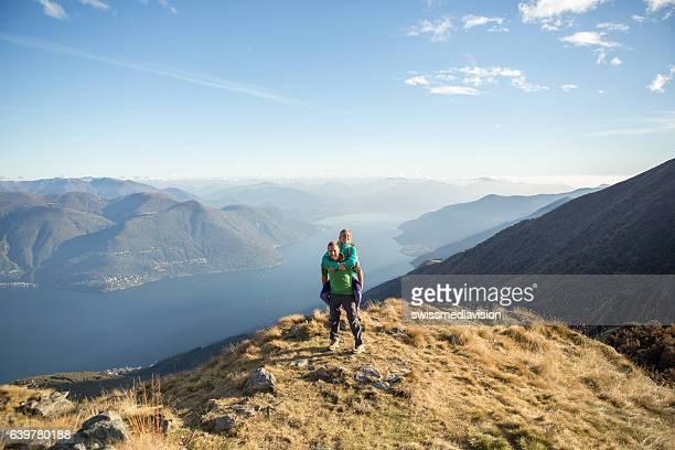 Playful young couple on mountain top, piggyback