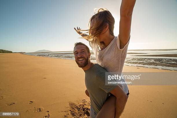 Playful young couple on the beach at sunset