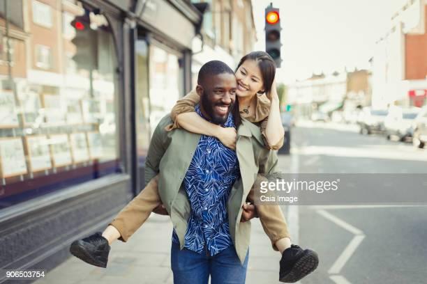 Playful young couple piggybacking on urban street