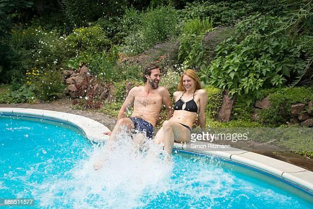 Playful young couple splashing in swimming pool