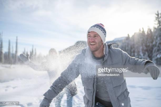 jeunes couples ludiques jetant des boules de neige à l'autre au coucher du soleil ayant l'amusement et appréciant des vacances d'hiver - wintersport photos et images de collection