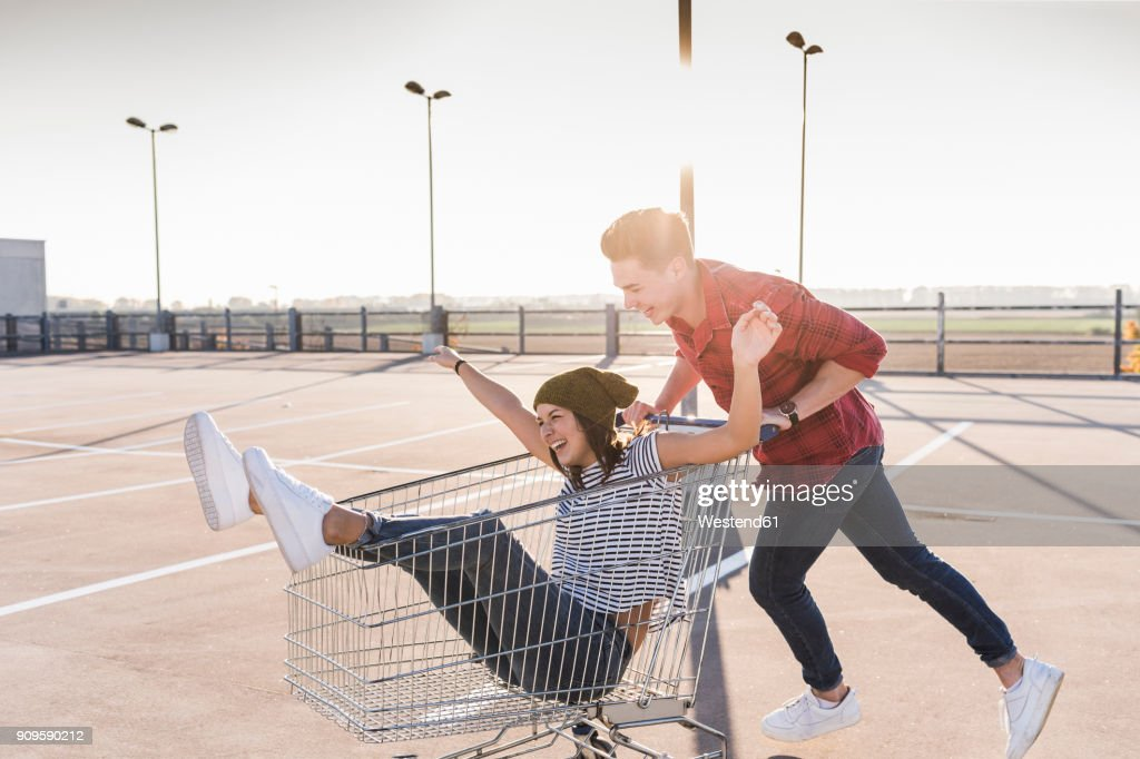 Playful young couple with shopping cart on parking level : Stock-Foto