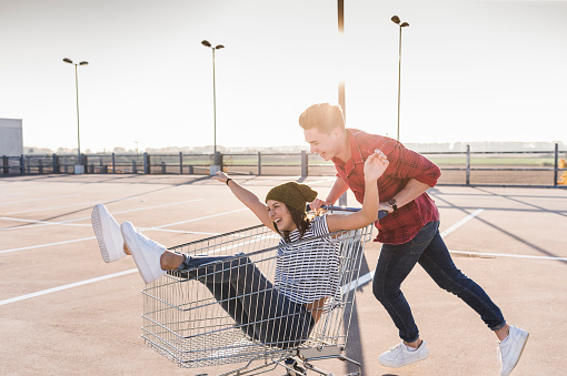 Playful young couple with shopping cart on parking level - gettyimageskorea