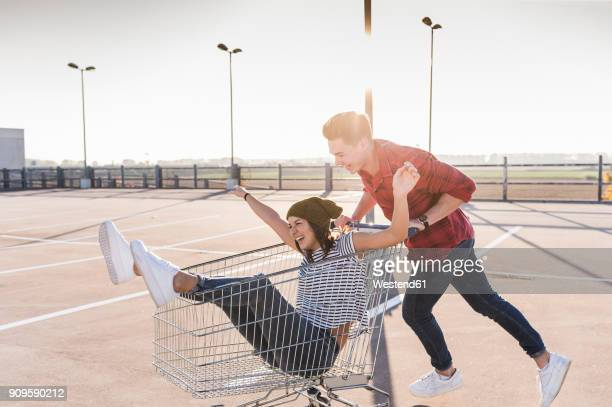 playful young couple with shopping cart on parking level - freiheit stock-fotos und bilder