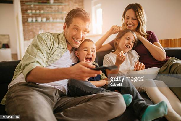 playful young family watching television - kanaal stockfoto's en -beelden