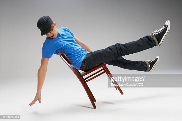 Playful young man balancing himself on a chair