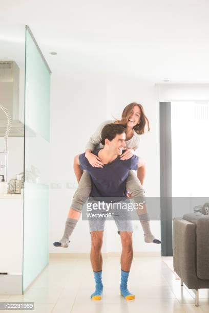 playful young man carrying girlfriend piggyback at home - genot stockfoto's en -beelden