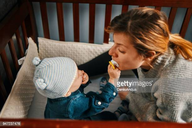 playful young mother and her baby - pacifier stock pictures, royalty-free photos & images