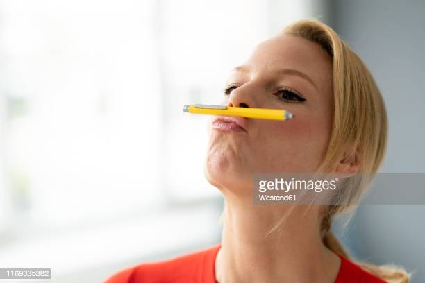 playful young woman balancing pen on her mouth in office - abgelenkt stock-fotos und bilder