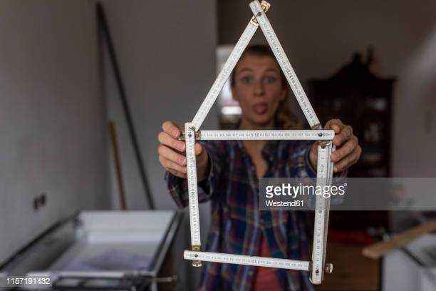 playful young woman holding pocket rule in shape of a house - bricolage humour photos et images de collection