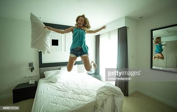 Brincalhão jovem saltar na cama-Luta de Almofada