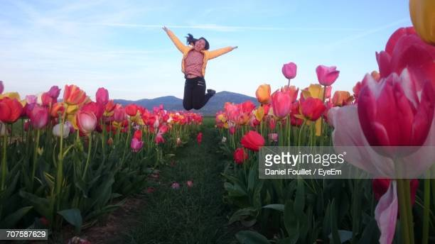 Playful Young Woman Jumping On Tulip Field Against Sky