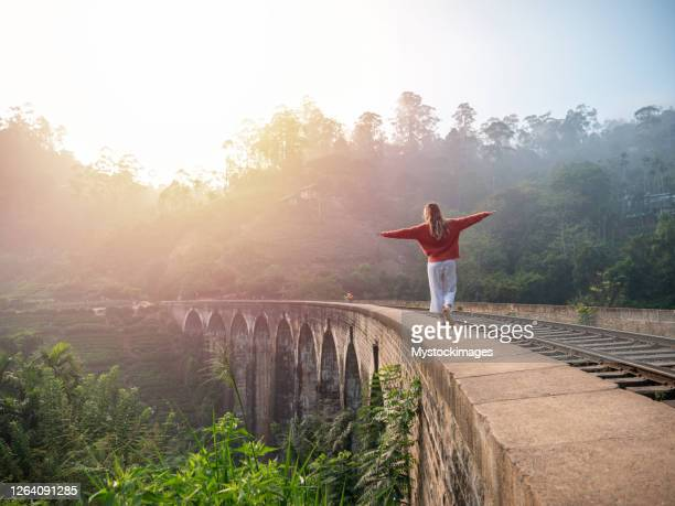 playful young woman walking on the edge of ancient viaduct bridge - sri lanka stock pictures, royalty-free photos & images