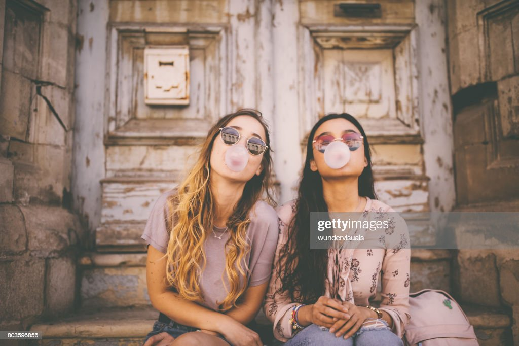 Playful young women blowing pink bubble gums in old city : Stock Photo