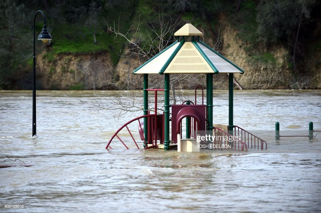 A playground is seen submerged in flowing water at Riverbend Park as the Oroville Dam releases water down the spillway in Oroville, California on February 13, 2017. Almost 200,000 people were under evacuation orders in northern California Monday after a threat of catastrophic failure at the United States' tallest dam. Officials said the threat had subsided for the moment as water levels at the Oroville Dam, 75 miles (120 kilometers) north of Sacramento, have eased. But people were still being told to stay out of the area. / AFP / Josh Edelson