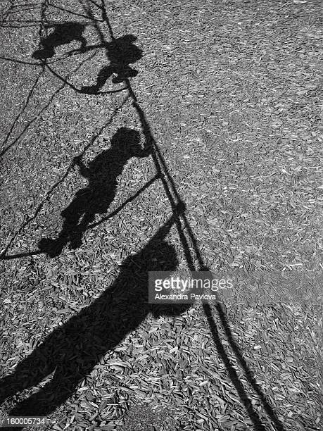 playground shadows of children climbing ropes - alexandra pavlova stock pictures, royalty-free photos & images