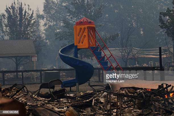A playground slide stands undamaged among smoldering rubble during the Valley Fire on September 13 2015 in Middletown California The fastmoving fire...