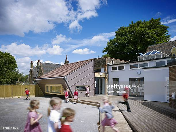 Playground view of extension school children playing Dulwich Village Infant School London United Kingdom Architect Cazenove Architects 2012