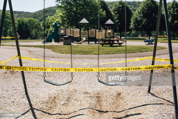 playground with caution tape: park closed, playground closed during covid-19 coronavirus pandemic - cordon tape stock pictures, royalty-free photos & images